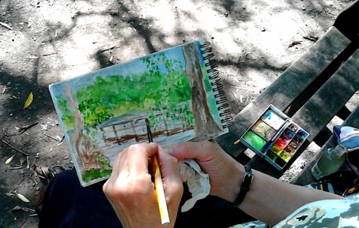 A close up of my hands doing my open air sketching at the scene . You can just see my little  watercolour sketching kit .