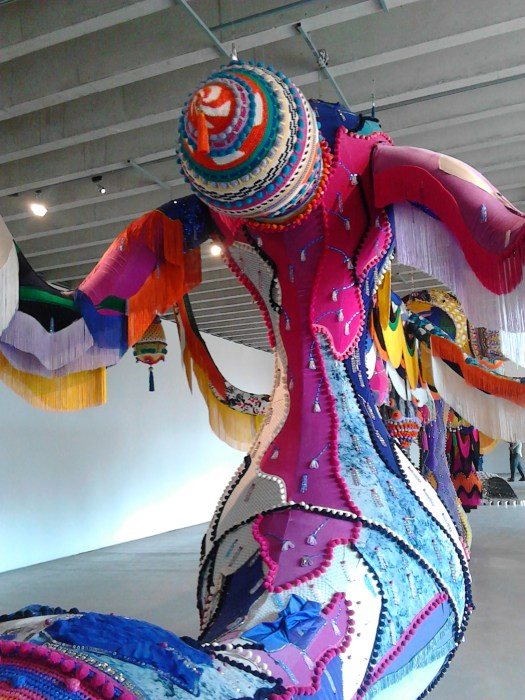 A huge soft sculpture  covered in appliqued,  embroidered fabric in the shape of a female figure  - one of the installations in the sculpture exhibition