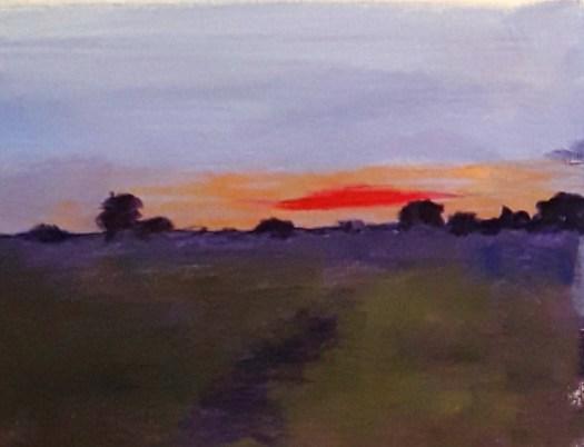 The sun setting in a blaze of glory over a moorland scene.