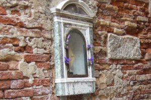 Outdoor shrine embedded in a wall in Venice Photo by Margie Miklas