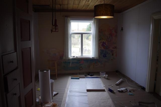Über den Spannkarton muss man Papiertapeten leimen, weil die neuartigen Non-Woven-Tapeten sich nicht mit der Feuchtigkeit ausdehnen und wieder zusammenziehen, was zu Rissen führen würde. An der Hinterwand sieht man noch das Wandbild, das unsere Freunde für uns gemalt haben.