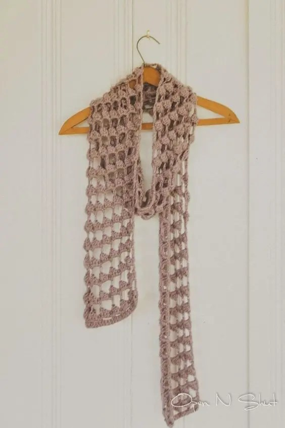 A purple triangle stitch scarf hanging on a wooden hanger