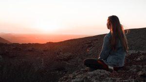 woman in blue denim jacket sitting on rock during sunset