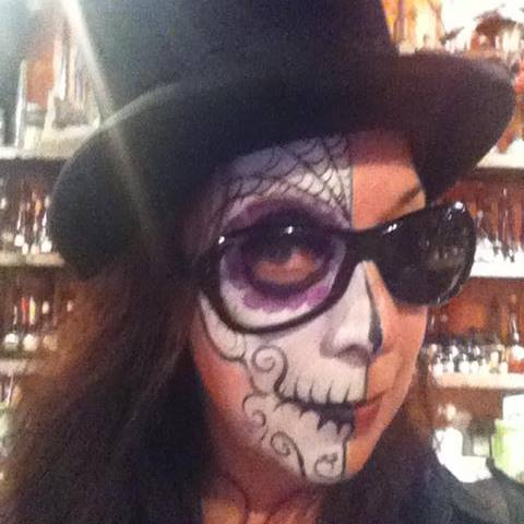 A woman's face half-painted like a skeleton wearing sunglasses missing a lens and a top hat.