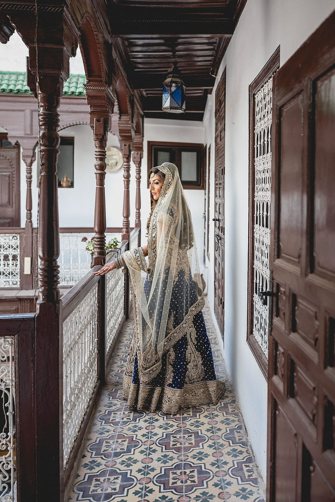 Bride looks over the balcony at her Traditional Moroccan Destination Wedding