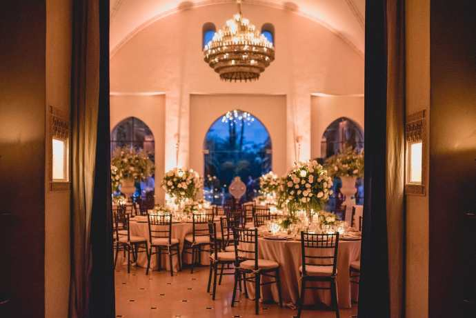 An image taken through the door into the dining room, showing the impressive luxurious chandelier and some of the large floral centrepieces