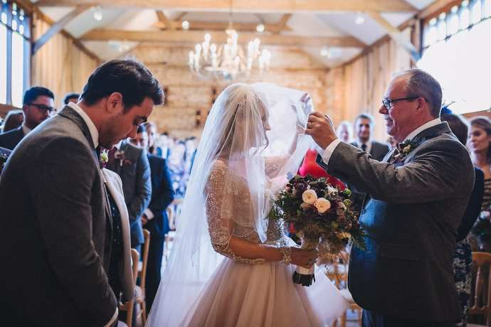 The bride's father lifts her veil from her face as she reaches the end of the aisle