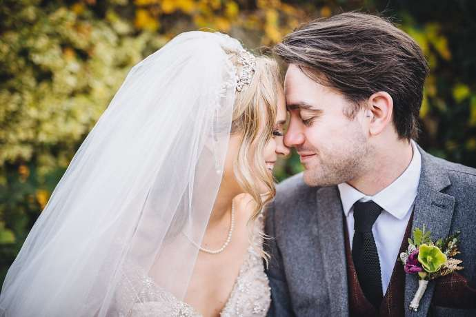 The bride leans and rests her forehead against her groom's