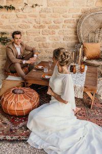 robe de mariée bustier, cape transparente, chignon mariée, costume camel, fauteuil rotin, pouf orange, décoration mariage bohème, mariage bohème, magazine, inspiration mariage bohème