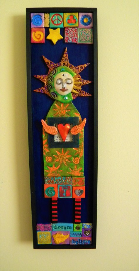Polymer clay mosaic wall art of a sun goddess with a winged heart.