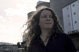Porträtt på Maria Niemi utomhus. Det lockiga håret lyfter av vinden. Foto: Anna Drvnik
