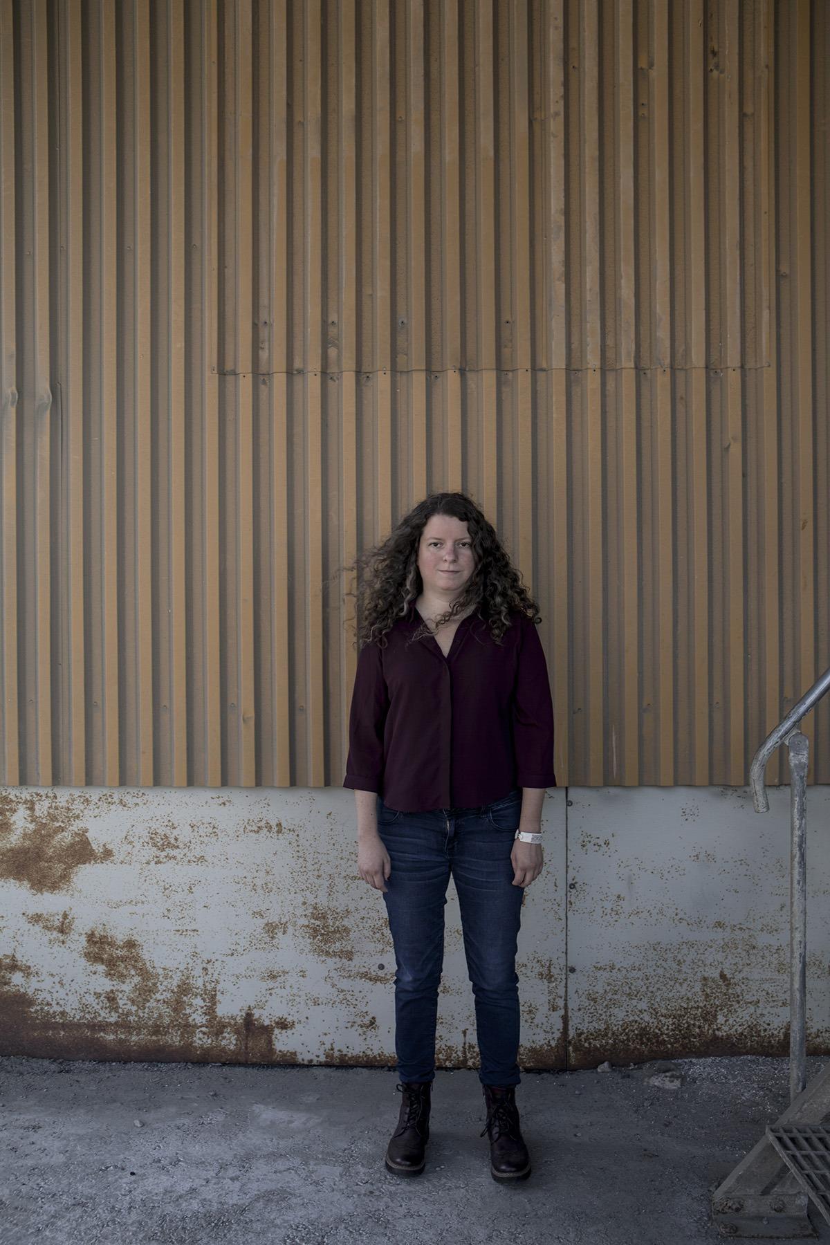Porträtt på Maria Niemi ståendes framför en gul plåtvägg. Maria har på sig jeans och en vinröd skjorta