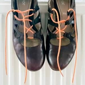"""Foto van schoenen met oranje veters op een verwarming bij het gedicht """"Oranje 3""""."""