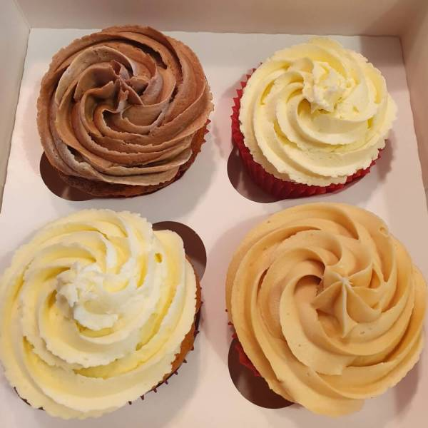 Box of assorted cupcake flavours with big swirls of buttercream