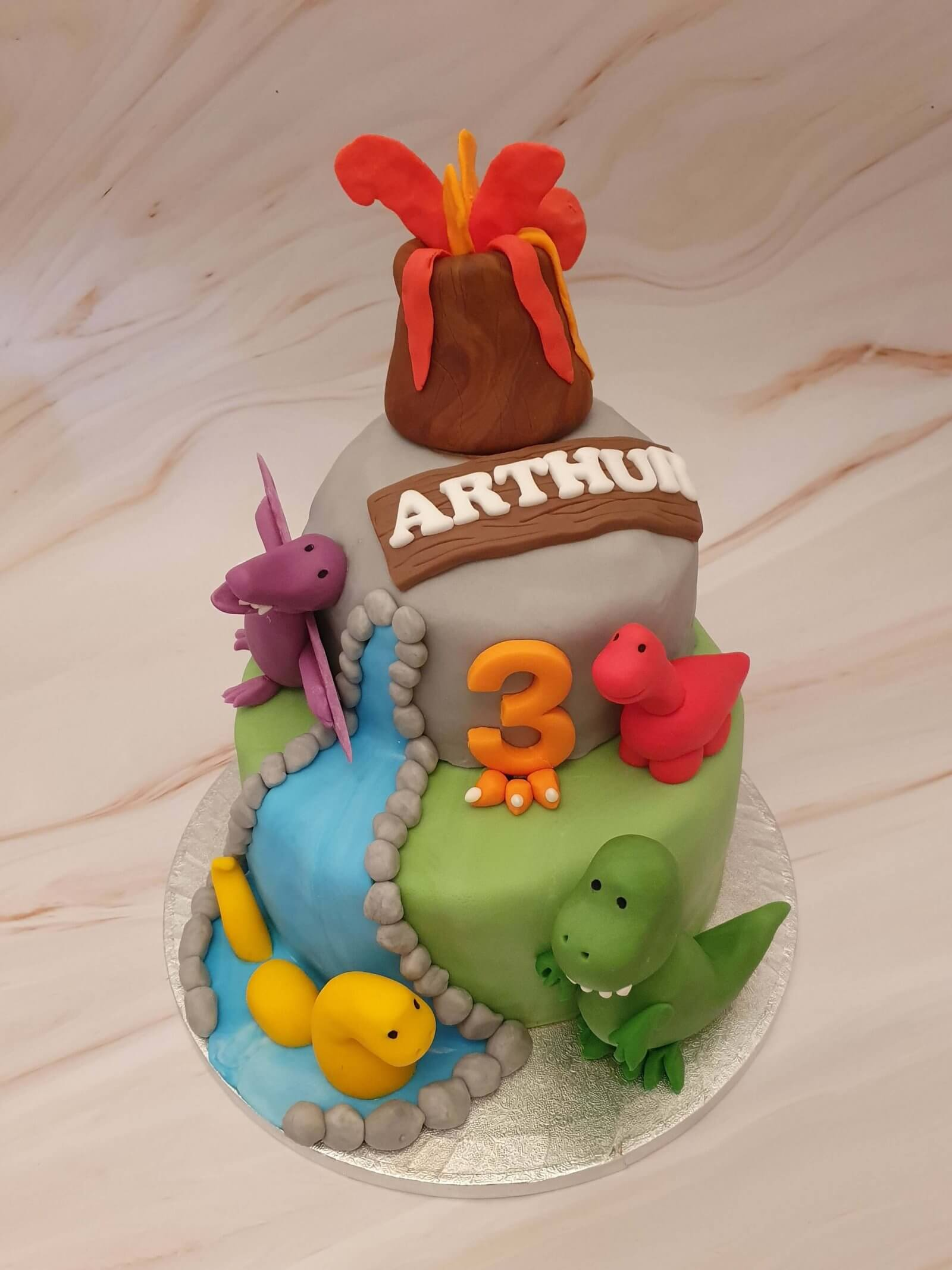 Bespoke Dinosaur Children's Birthday Cake delivery Milton Keynes with multi coloured dinosaurs and an exploding volcano on top