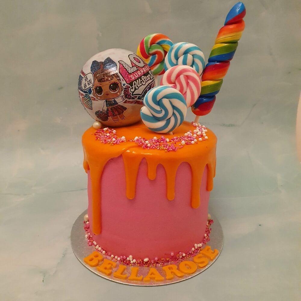 Lol surprise children's birthday cake in bright pink buttercream icing and orange drip