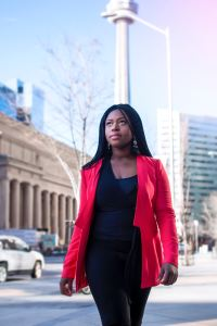 Picture of black woman walking down a city street in a black pant suit and bright red jacket in article by Marie Deveaux about women who want to have it all