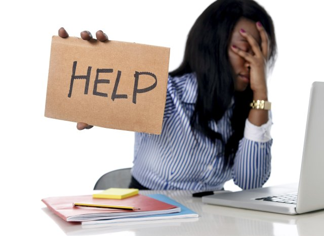 "Black business woman sitting at a desk over her laptop with cardboard ""help"" sign as she buckels udner the weight of her responsibilities as a business owner. Image on mariedeveaux.com, career coaching for women of color."
