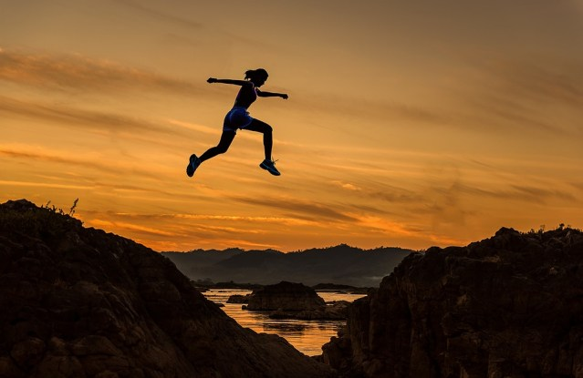 "Image of woman leaping a chasm with a sunset backdrop as featured on article on mariedeveaux.com career counseling website ""why job hopping works"" about leap frogging in your career"