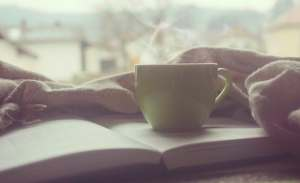 image of a journal with a hot cup of copy resting atop it in the earlymorning in article from career coach marie deveaux about benefits of early rising 4am is the new 6 am
