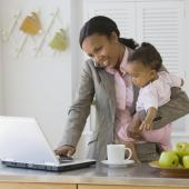 Black mom balancing her baby and getting work done on a laptop as Marie Deveaux, career coach and trainer discusses using LinkedIn in 5 minutes a day to grow your network