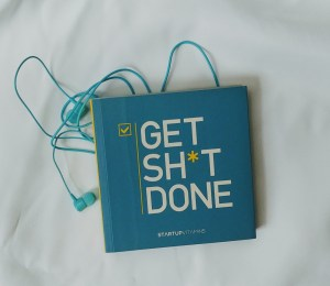 """Image of the book """"Get Sh*t Done"""" and a set of earbuds againast a whit ebackground on mariedeveaux.com career and life coach talking about productivity and efficiency"""