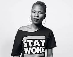 """Luvvie Ahayi pictured in black and white in a """"stay work"""" t shirt as Marie Deveaux career coach speaks about the power of community for Black women in America"""