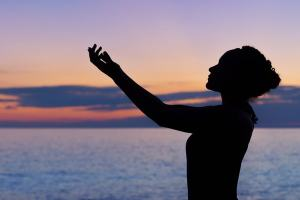 Marie Deveaux CAreer coach describes wasy for soloreprneurs to keep networking a priority by focusing on their internal work as much as their external. Image of a woman's silhouette against a sunrise with her arms outstretched in a receiving posture.