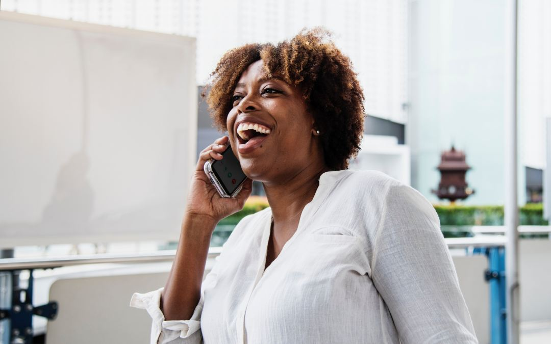 Black woman smiles enthusaistically as she holds a phone up to her ear, seemingly connecting with some one in a genuine way. Marie Deveaux career coach describes 6 ways to get good at networking to build your solopreneur business