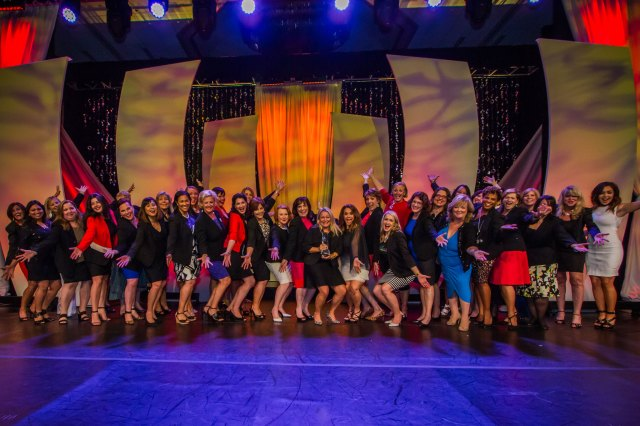 A backlit stage features dozens of women in business attire smiling with open arms outstretched at the ewomen conference 2017 held in Dallas Texas. Part of banner to article about the 2018 conference as written by career and communications coach, Marie Devaux