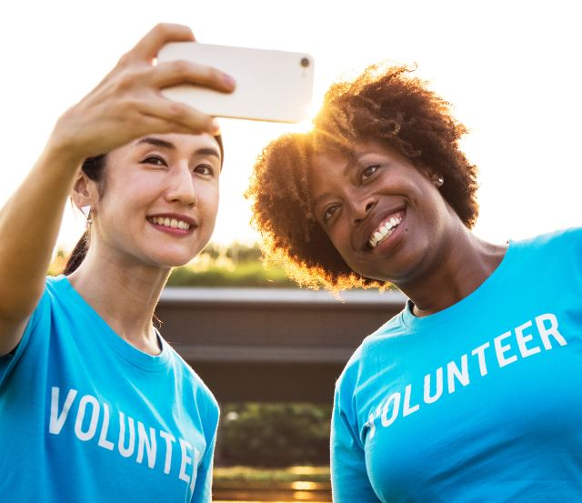 """A black woman and an Asian woman wearing blue shirts with the word """"volunteer"""" across their front smile and pose for a selfie together in the setting sun as Marie Devaeux hails tha value of giving of your time in order to receive more opportunities."""