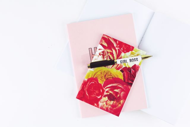 "Picture of a red coloreful notbeook atop a pink book and nea r a pen that reads ""girl boss"""