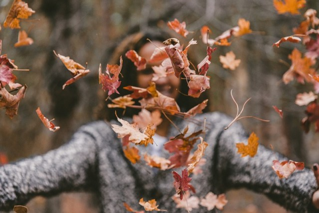 black woman throws fall leaves in the air in excitement in article on mariedeveaux.com on how to build small business momentum in the Fall
