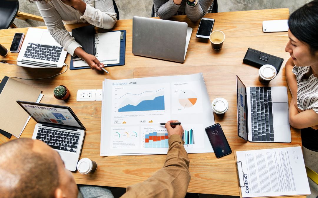 Image of a conference table with multiple people's hands gesturing towards financial projections as Marie Deveaux small business coach for women of color explains how to craft 90 day plans in 4 easy steps