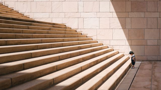 A toddler stands at the base of a long set of stairs as Marie Deveaux business coach describes how setting small steps for every entrepreneur builds to larger annual goals.