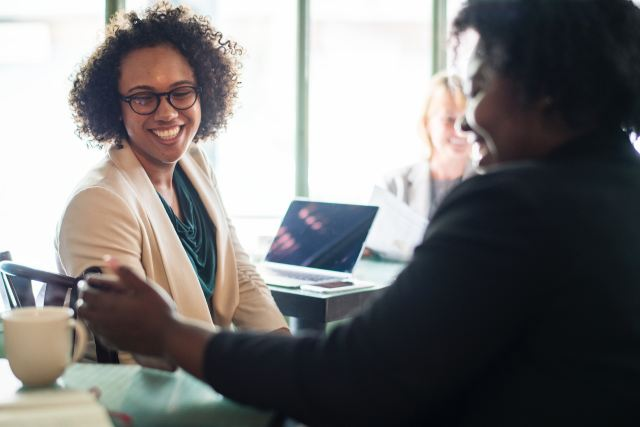 A smiling Black woman sits at a desk infront of another WOC colleague as Marie Deveaux describes the 5 components of SMART goals and how to use them to drive traffic to your small business