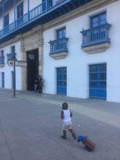 Kid playing in front of Casa de la Artesania