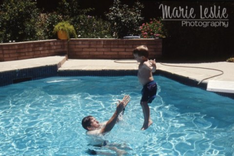 little boy jumping into a pool