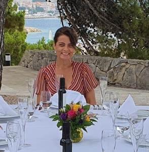 Marijana Brdar sitzt am gedecktem Essenstisch.