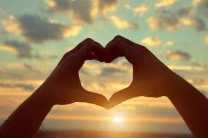 Zwei Hände bilden ein Herz. Gezeigt über den Himmel.