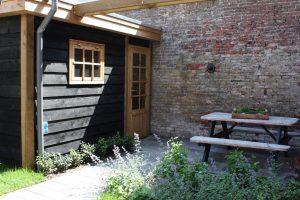 de toegang vanuit de steeg naar de tuin is via het op maat gemaakte tuinhuis