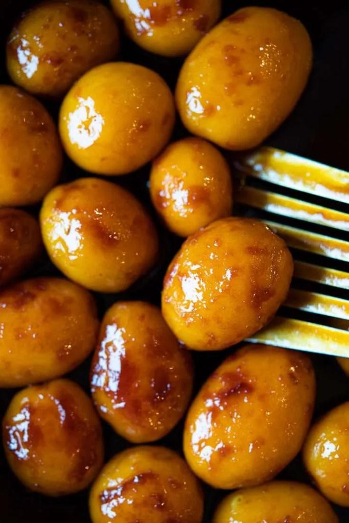 De brunede kartofler vendes i karamel massen på panden