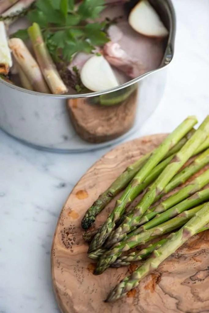 De grønne asparges har fået knækket enderne af og ligger på et skærebræt. I baggrunden kogelagen hvor man blandt andet kan se asparge enderne.