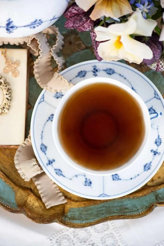 Te kop på bakke omgivet af forårsblomster og med et kors. Til Store bededag skal der nemlig drikkes te sammen med hvederne