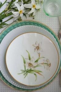 Bordet er dækket til pinse bla med en tallerken med pinseliljer