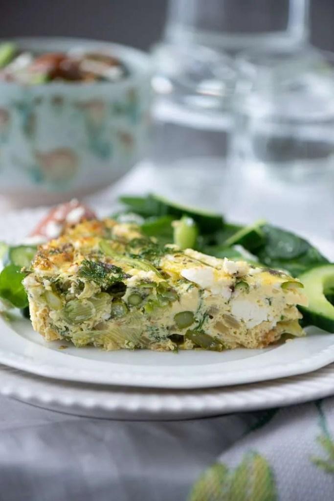 Et stykke asparges frittata på en tallerken så man kan se tværsnittet og de mange stykker asparges