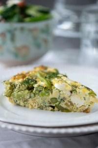 Et stykke frittata på tallerken så man kan se hvor let og luftig frittaten er samt stykker af asparges og feta