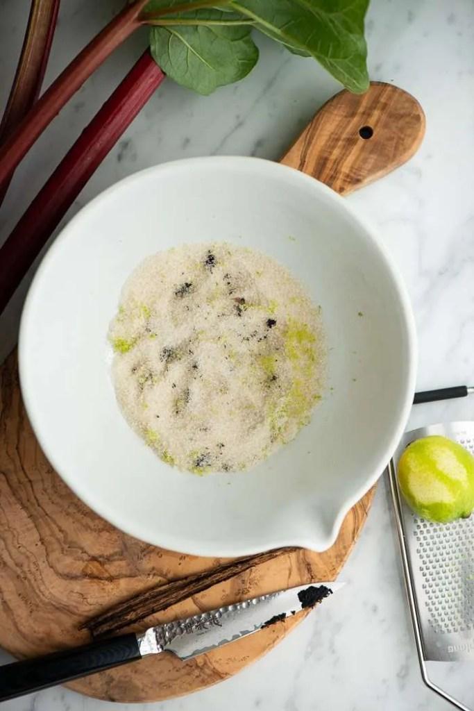 Lime - vanilje sukker til ovnbagte rabarber. På billedet kan man se hvordan limeskal og vanilje er gnedet ud i sukkeret og også hvordan limeskallen er revet på microplane rivejern mens en kniv har skrabet kornene ud af vaniljebælgen