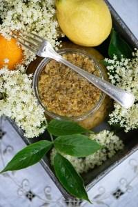 Glas med hyldeblomst marmelade omgivet af citroner og hyldeblomster