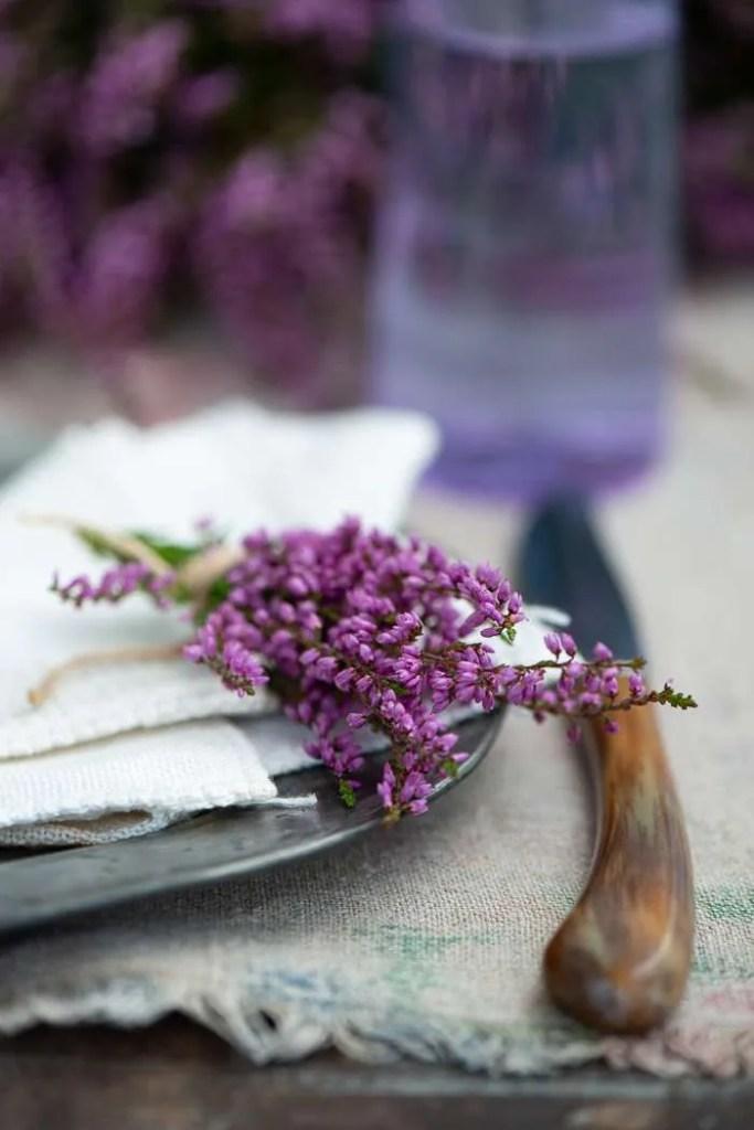 Et bord dækket med små lyng buketter